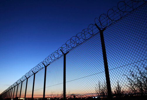 Barb wire fence at dusk - protection of Warsaw airport area (Poland).